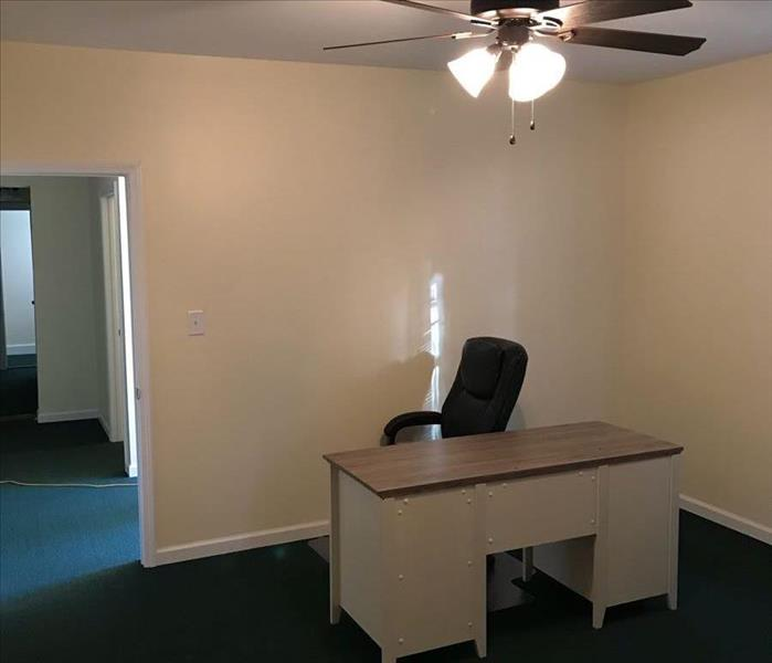 Pastor's office in repaired church, freshly painted walls, new carpet and new desk