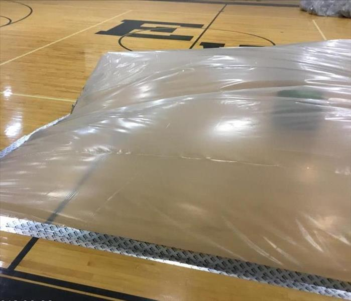 gym floor with plastic containment over wet area