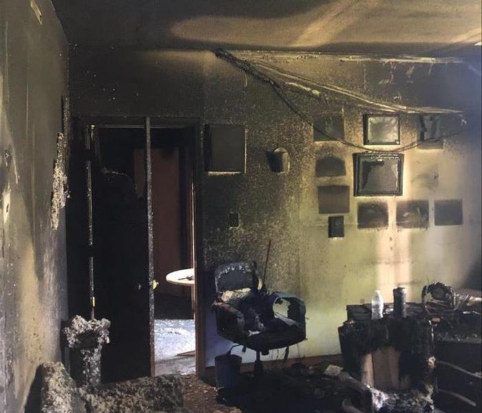 Pastor's office in church, walls are severely charred, insulation has fallen from overhead