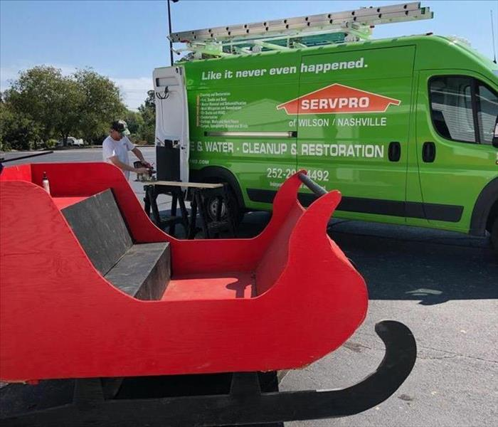 Red Santa sleigh is positioned in front of a Servpro van. A Servpro employee is cutting wood that will be used on the sleigh