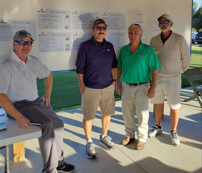 Franchise owner stands with 3 other teammates in front of score chart at golf course