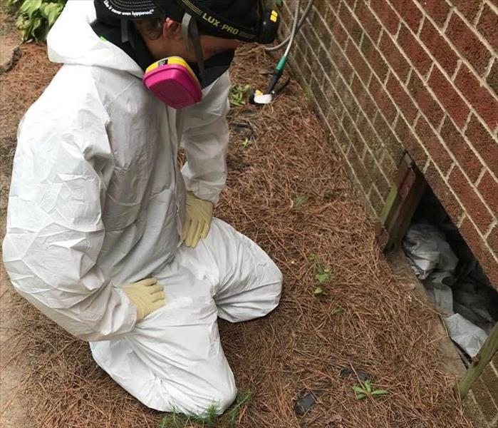 SERVPRO technician wearing personal protective equipment, kneeling in front of crawlspace