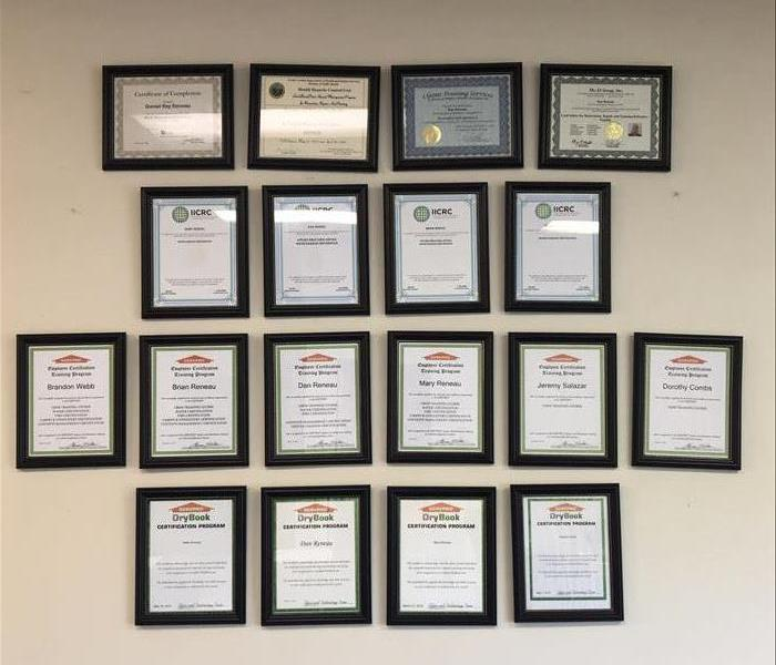Rows of framed certifcates on wall